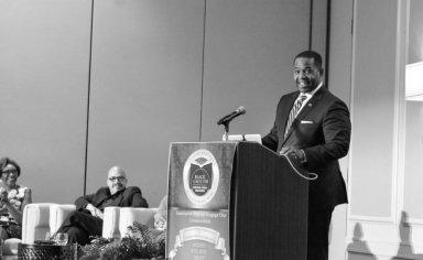 man speaking in front of people in seminar
